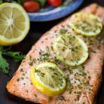Baked Steelhead Trout Fillet with three sliced lemons sprinkled with a green herb