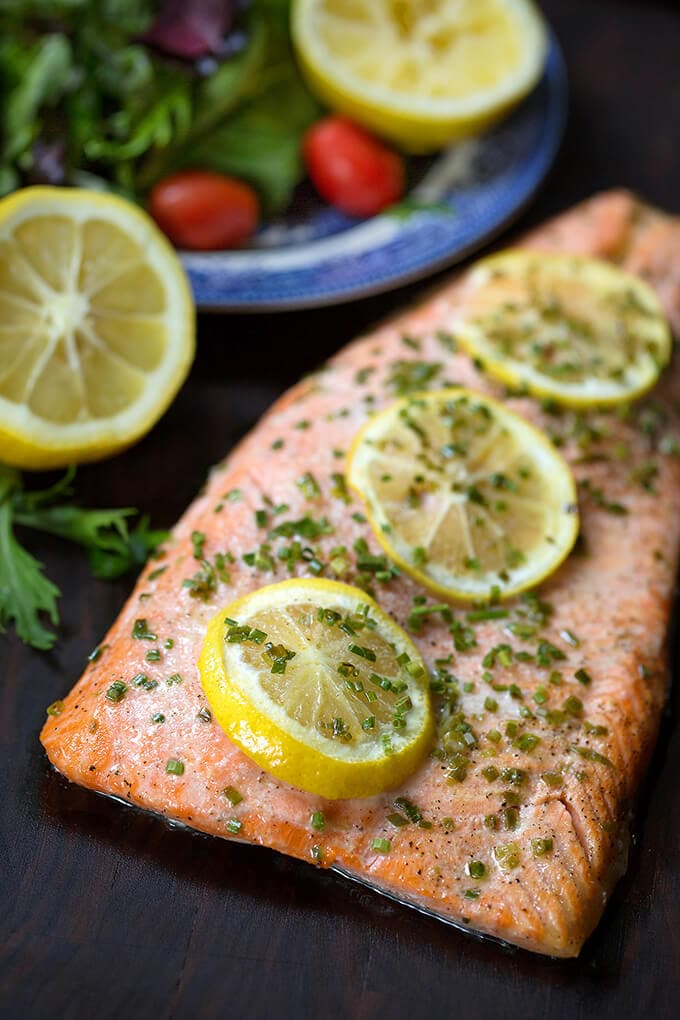 Baked Steelhead Trout with 3 lemon slices sprinkled with green herb on a wood board