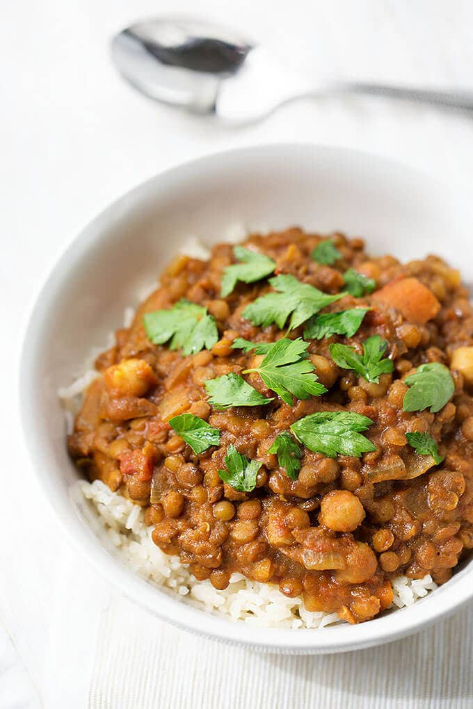 Crock Pot Curry Lentils over rice in a small white bowl