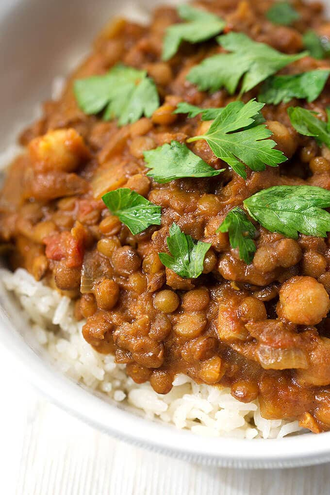 Close up of Crock Pot Curry Lentils over rice in a small white bowl