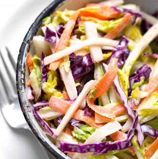 This Easy Creamy Coleslaw recipe is a tasty coleslaw with a creamy, tangy-sweet dressing. We like putting this coleslaw on top of pulled pork sandwiches. simplyhappyfoodie.com #coleslaw #coleslawrecipe creamy coleslaw recipe