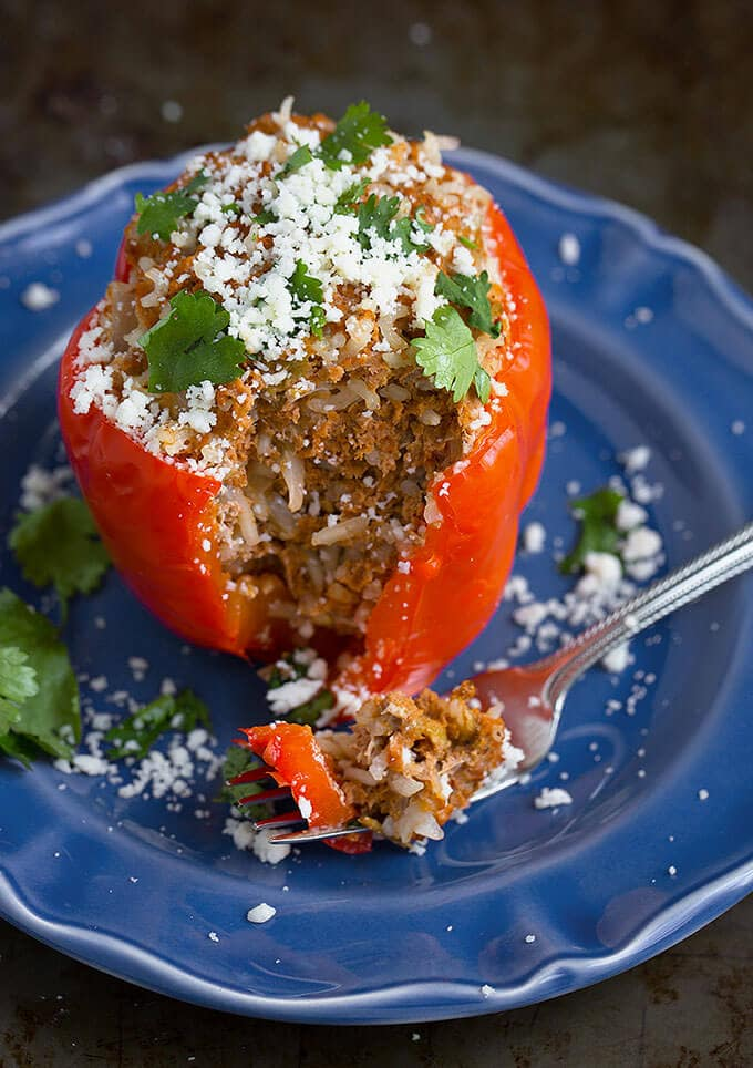Delicious Instant Pot Mexican Stuffed Peppers are so easy to make, and ready in under an hour! Great weeknight meal. simplyhappyfoodie.com #instantpotstuffedpeppers #pressurecookerstuffedpeppers