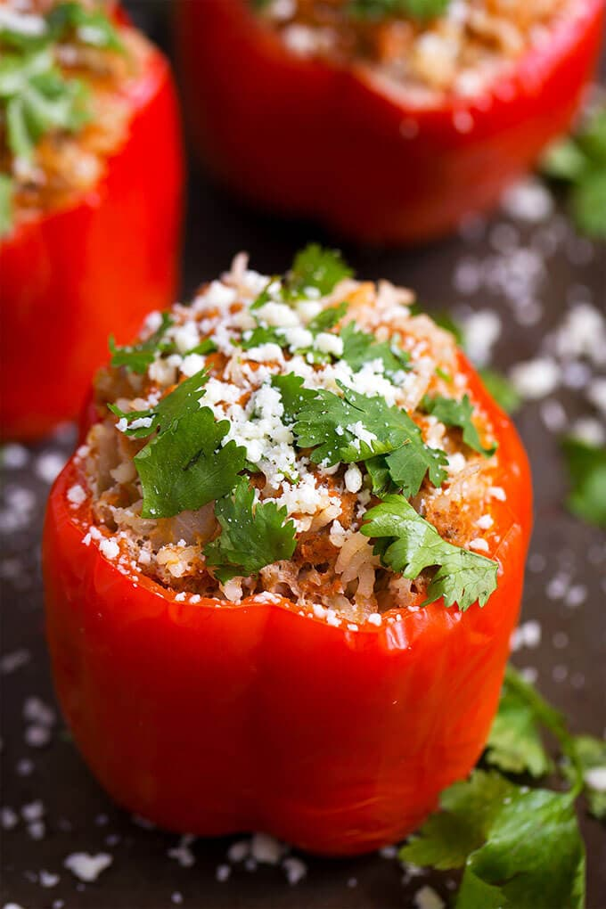 Three red Mexican Stuffed Peppers on dark background