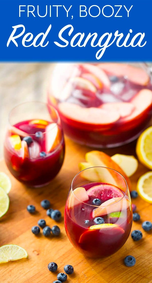 Fruity Red Sangria in a stemless wine glass with a pitcher behind it