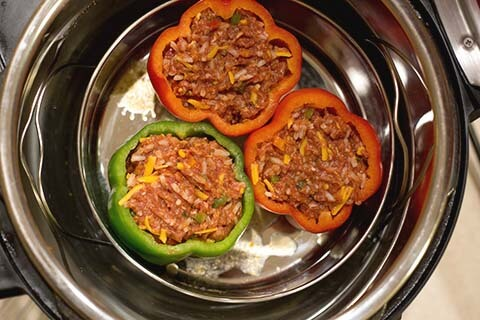 Instant Pot Stuffed Peppers are a great weeknight meal. A classic dinner of pressure cooker stuffed peppers in under an hour! simplyhappyfoodie.com #instantpotrecipes #instantpotstuffedpeppers #pressurecookerstuffedpeppers