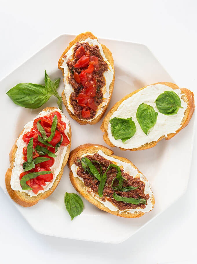 Four Bruschetta on white plate