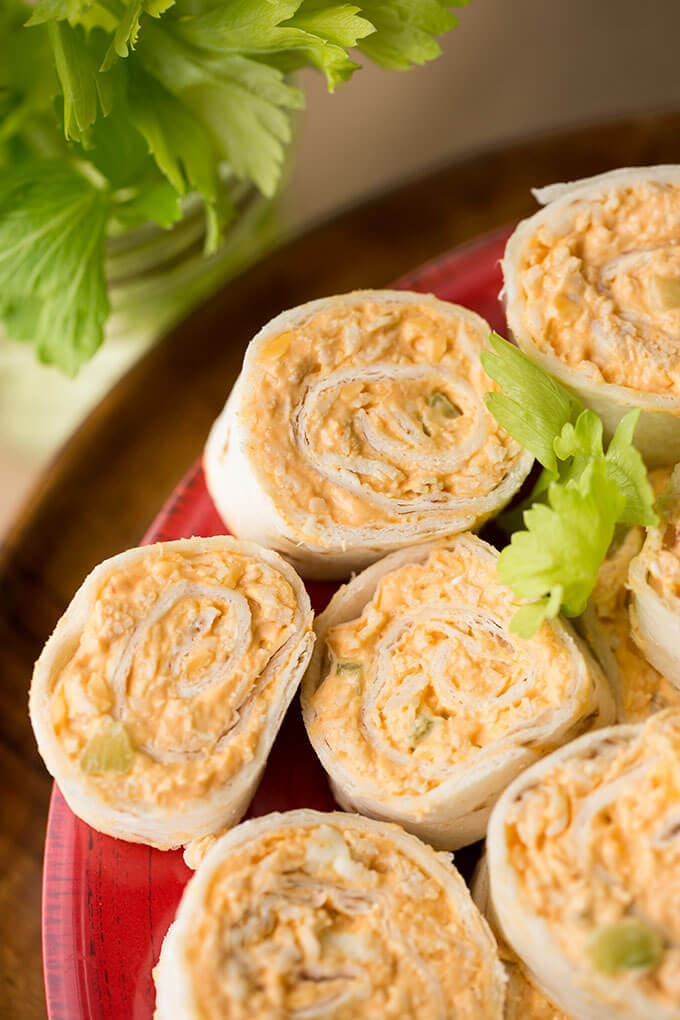 Buffalo Chicken Pinwheels have the wing flavor in a neat pinwheel appetizer. Great for a party or game day! simplyhappyfoodie.com #gamedayfood #pinwheelrecipe #buffalochicken