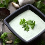 Cilantro Cream Dressing in small square black bowl garnished with cilantro