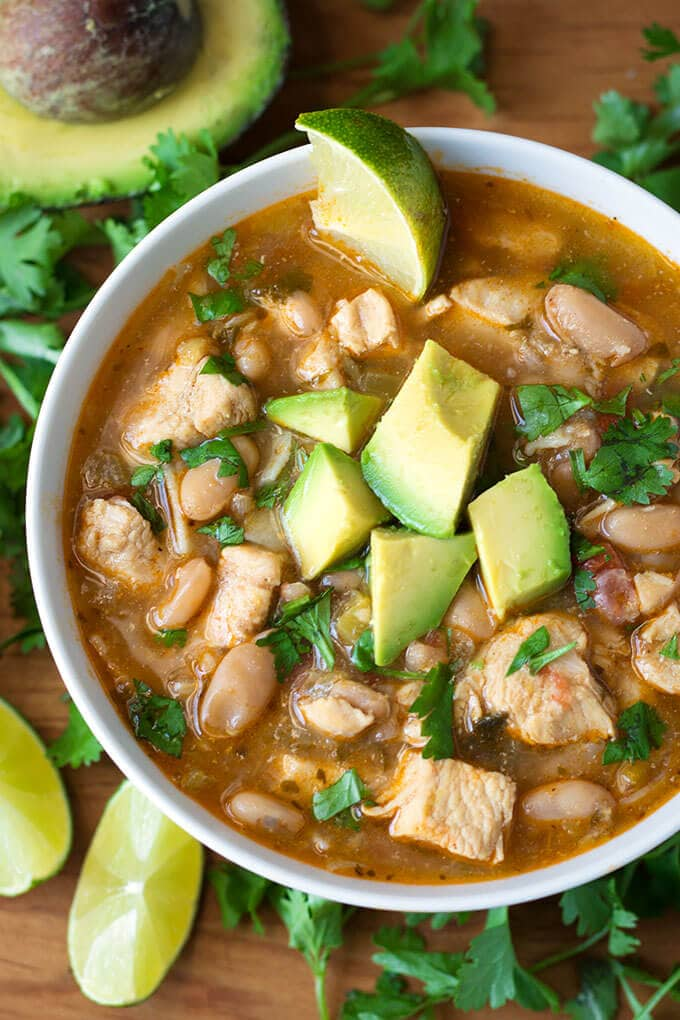 Instant Pot White Chicken Chili has a great Tex-Mex flavor with chicken, white beans, and green chiles. We love this pressure cooker white chicken chili with tortillas and avocado. simplyhappyfoodie.com #instantpotchili #whitechickenchili
