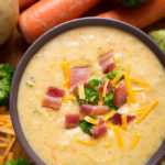 Loaded Broccoli Cheese & Potato Soup in a dark colored bowl with carrots and broccoli in the background