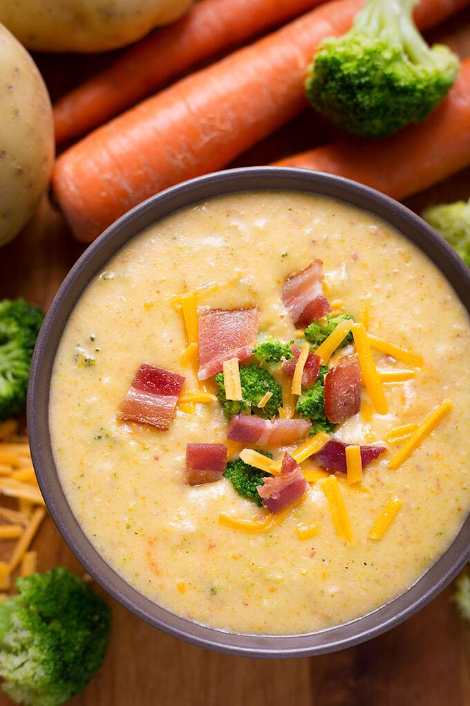 Loaded Broccoli Cheese & Potato Soup in small purple bowl with carrots and broccoli in background