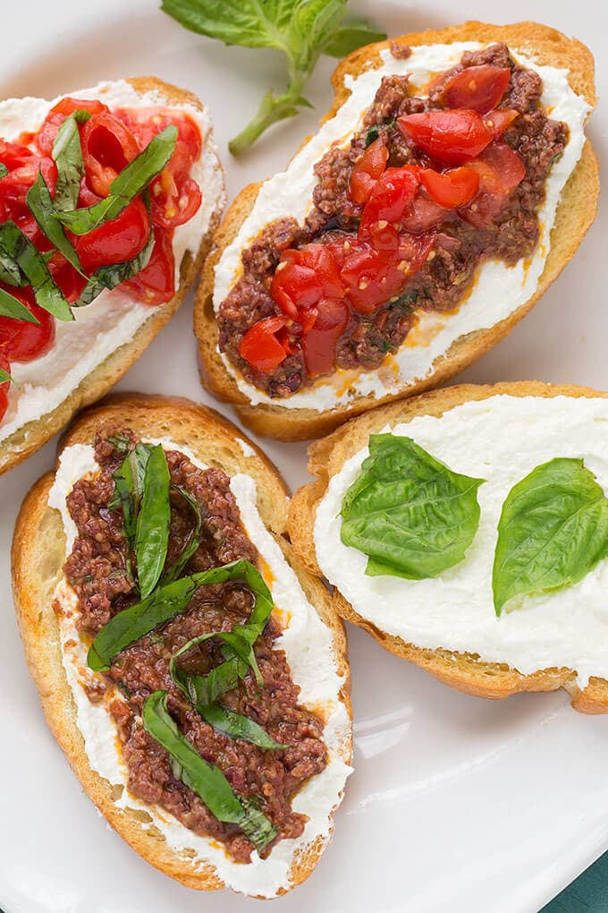 Four pieces of toasted bread with whipped feta spread and Olive Tapenade on white plate