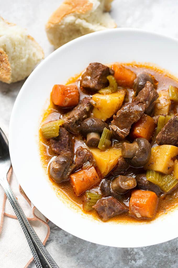 Sandy's Instant Pot Beef Stew in white bowl next to silver spoon and chunks of bread
