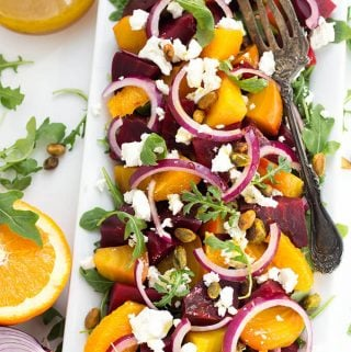 Beet Salad with Goat Cheese and Orange Vinaigrette also has red onion, and a sprinkling of pistachios. I like it on a bed of baby arugula. simplyhappyfoodie.com #beetsalad #beetsaladgoatcheese #beetsaladorangegoatcheese