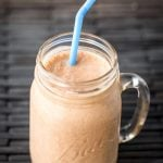 Chocolate Peanut Butter Banana Smoothie in glass Ball jar with blue straw