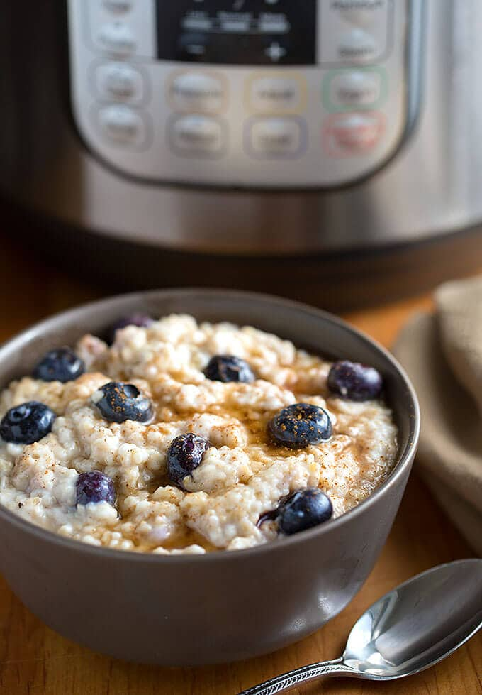 Steel Cut Oats in a dark grey bowl topped with blueberries with a pressure cooker in the background