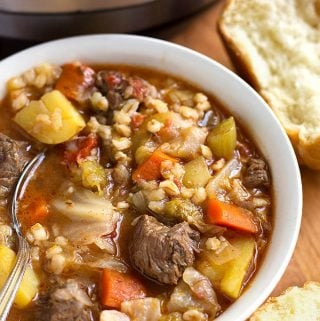Instant Pot Beef Barley Vegetable Soup in a white bowl with spoon next to two rolls
