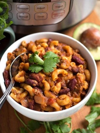 Chili Mac in a white bowl with spoon on wooden board