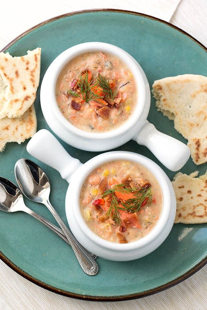 Two white bowls of Salmon Chowder on turquoise plate with two silver spoons and torn flat bread