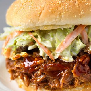 Slow Cooker BBQ Pulled Pork with coleslaw on hamburger bun on white plate