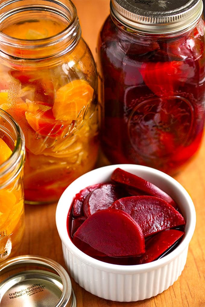 Pickled Beets in a small white bowl with canning jars in the back ground on wooden board