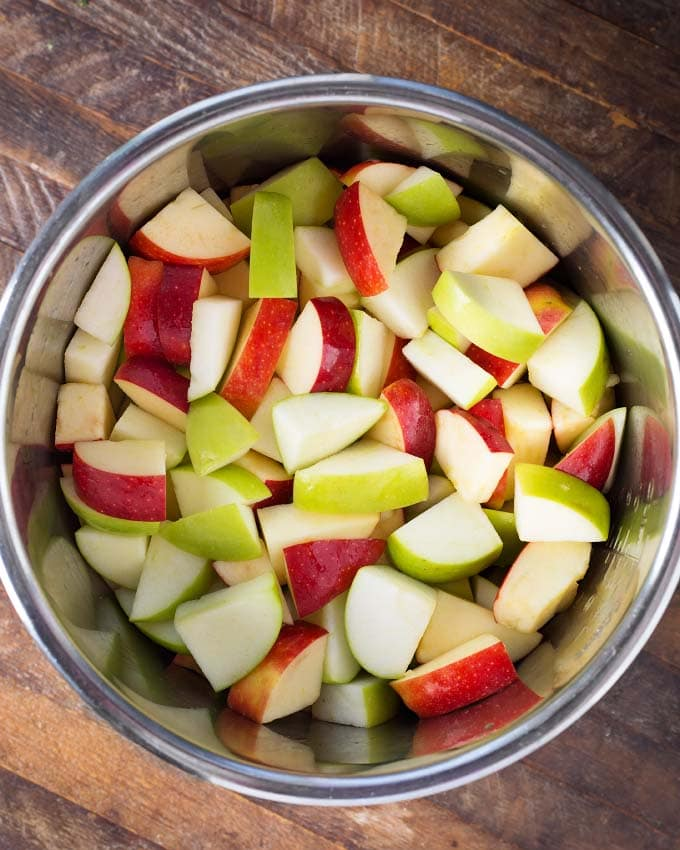 chopped red and green apples in pot on wooden board