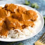 Butter Chicken over rice on white plate next to gold fork