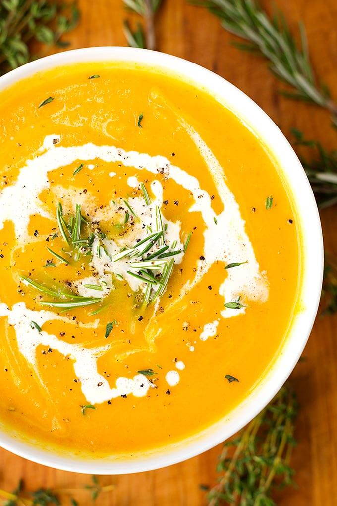Instant Pot Butternut Squash Soup in a white bowl surrounded by rosemary