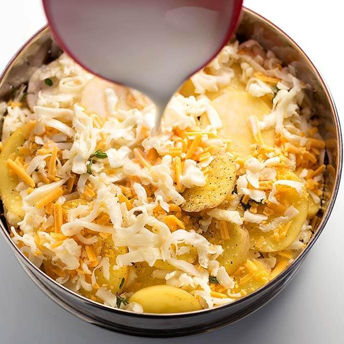 Sliced potatoes and cheese with white sauce pouring on top