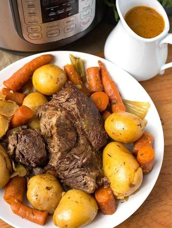 Pot Roast on a white plate next to a small pitcher of gravy and pressure cooker