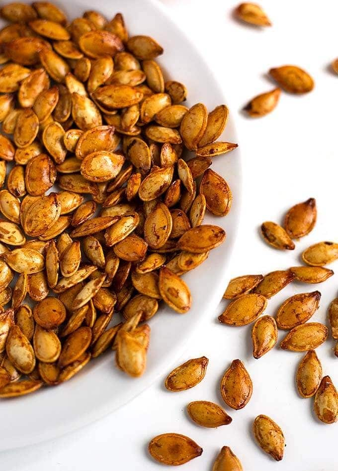 Roasted Pumpkin Seeds are a tasty and healthy snack. We enjoy them with different flavors, and this method works with all squash seeds. Roasted squash seeds are such a great treat! How to make roasted pumpkin seeds by simplyhappyfoodie.com #roastedpumpkinseeds #pumpkinseeds
