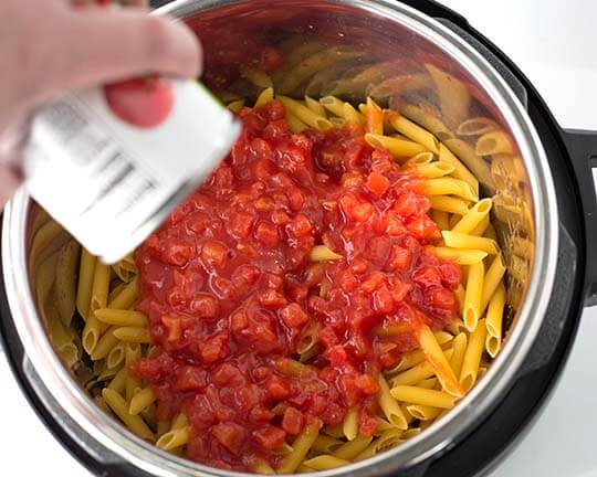 Diced tomatoes go over the pasta