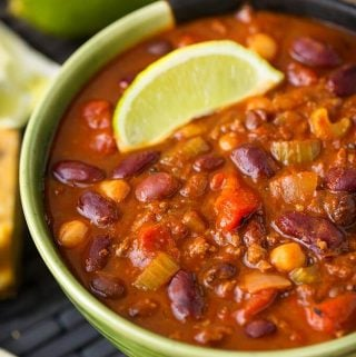 Chili in a two tone green bowl garnished with lime wedge