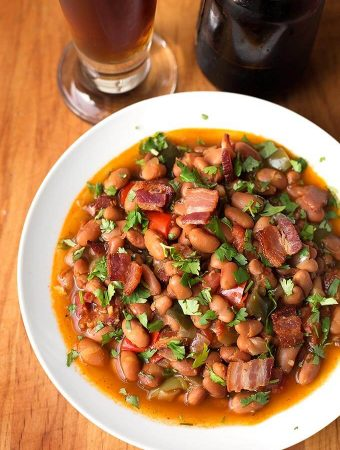 Instant Pot Drunken Beans, Frijoles Borrachos, have beer as part of the liquid, but they don't taste like alcohol. A savory blend of beans, bacon, spices, cilantro, and a little beer! simplyhappyfoodie.com #instantpotrecipes #instantpotpintobeans #instantpotdrunkenbeans #instantpotFrijolesBorrachos