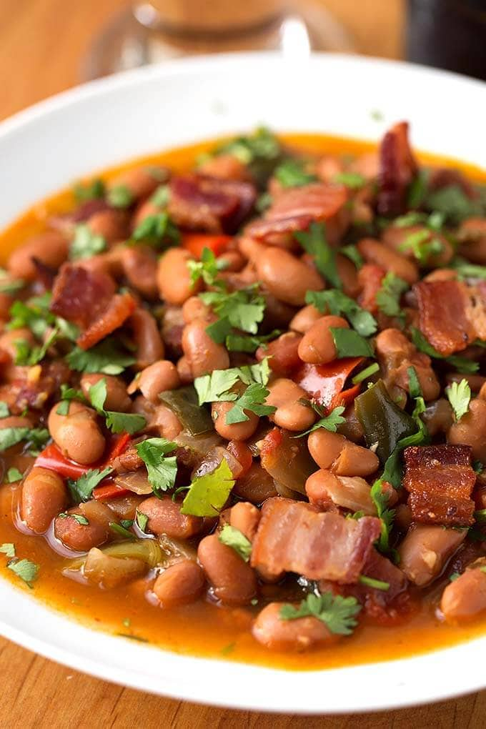 Instant Pot Drunken Beans, Frijoles Borrachos, have beer as part of the liquid, but they don't taste like alcohol. A savory blend of beans, bacon, spices, cilantro, and a little beer! simplyhappyfoodie.com #instantpotpintobeans #instantpotdrunkenbeans #instantpotFrijolesBorrachos