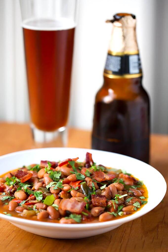 Drunken Beans (Frijoles Borrachos), in a white bowl next to glass of beer on a wooden board