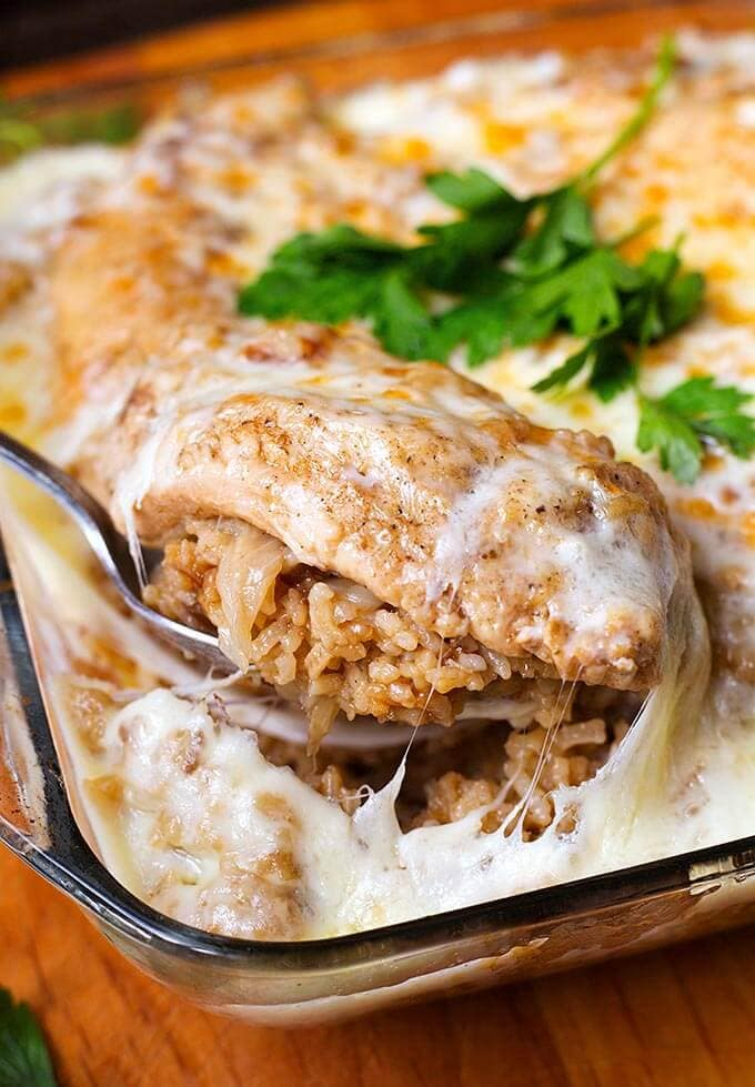 Silver spoon serving French Onion Chicken and Rice from glass casserole dish