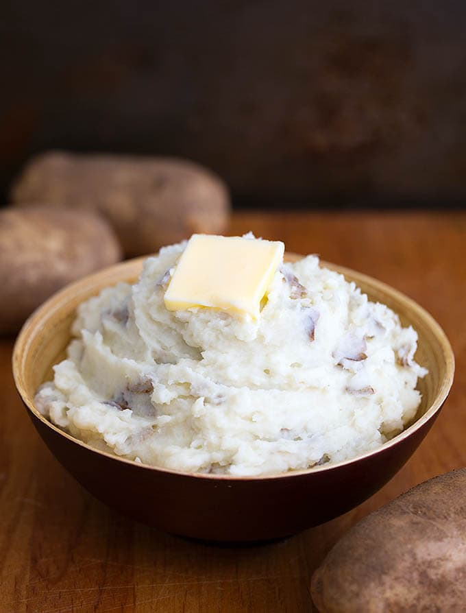 Mashed Potatoes with a slice of butter,in a brown bowl