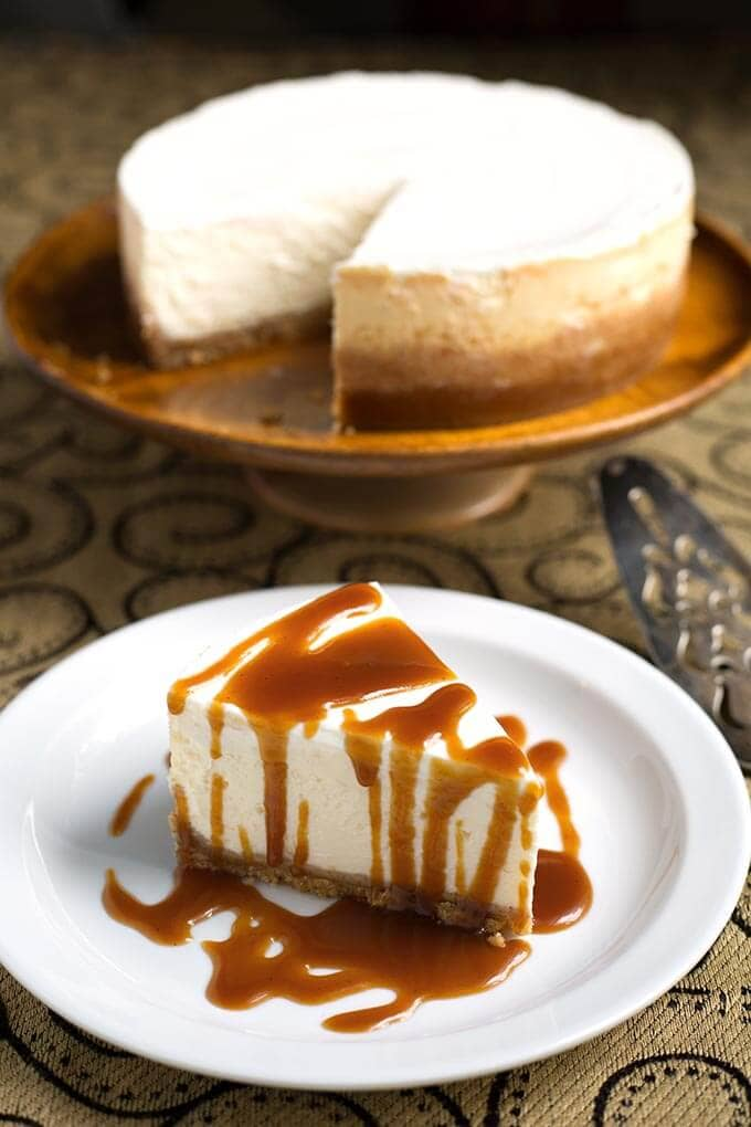Slice of New York Cheesecake drizzled with caramel sauce on white plate with rest of cake in the background