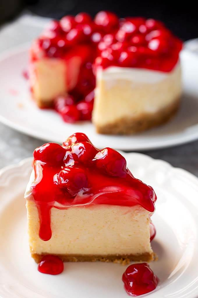 Slice of New York Cheesecake covered with cherry topping on a white plate with the rest of the cake in the background
