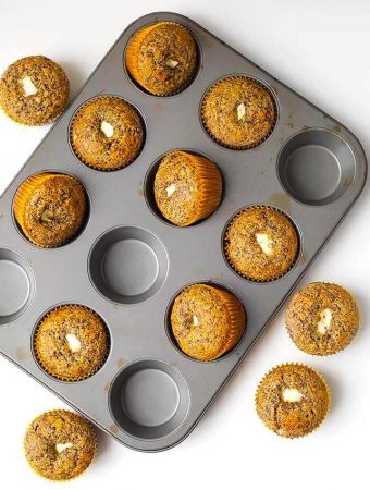 Orange Chocolate Cream Cheese Muffins in a muffin pan on a white background