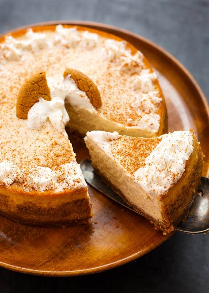 Eggnog Cheesecake on a wooden plate with a slice being removed