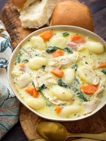 Creamy Chicken Gnocchi Soup on a wooden board with two rolls next to two golden spoons