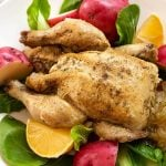 Cornish Game Hen on a white plate with potatoes and vegetables