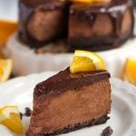 Slice of Instant Pot Chocolate Orange Cheesecake on a white plate garnished with orange slices and chocolate chips
