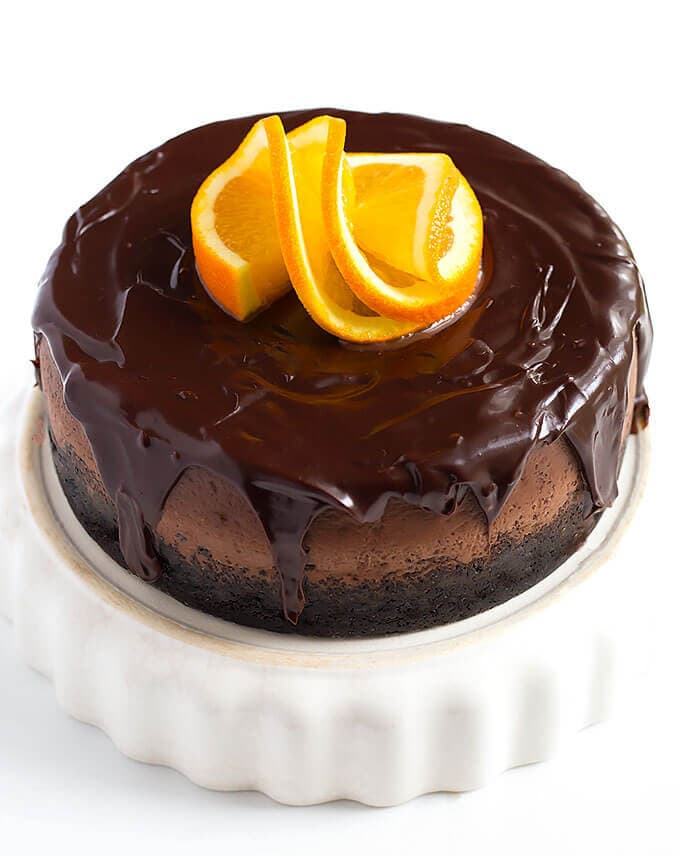 Instant Pot Chocolate Orange Cheesecake on a white serving dish garnished with sliced orange