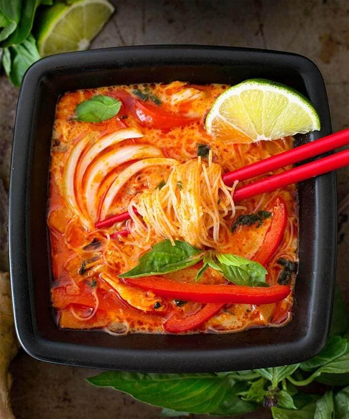 Coconut Red Curry Noodle Soup in black square bowl with red chopsticks