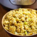 Instant Pot Cornbread Stuffing in a beige bowl with pressure cooker in background