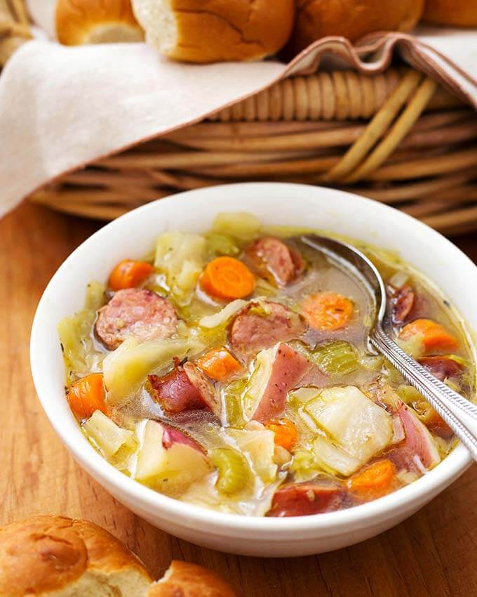 Hearty Kielbasa Cabbage Potato Soup in a white bowl with spoon with basket of rolls in background