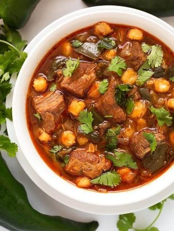 Instant Pot Posole - Pork Stew is Posole with a few extras. Poblano chile peppers and chipotle make this a spicy one pot meal. ¡Es muy deliciosa! simplyhappyfoodie.com #instantpotrecipes #instantpotposole #instantpotpozole #instantpotporkstew #pressurecookerrecipes